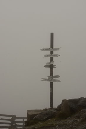Sign post at the peak poiting out whta hides behind the clouds